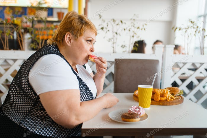 Fat woman eating doughnuts in fastfood restaurant
