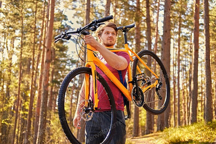 Positive sporty male holds mountain bicycle on a shoulder.