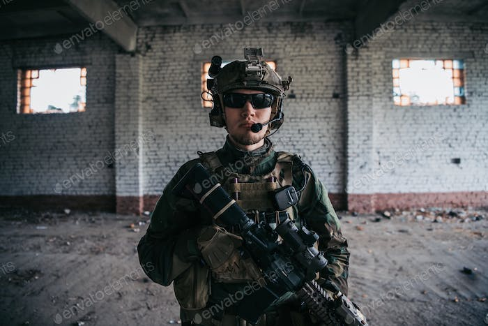 Close-up of a professional fully equipped soldier looking at camera