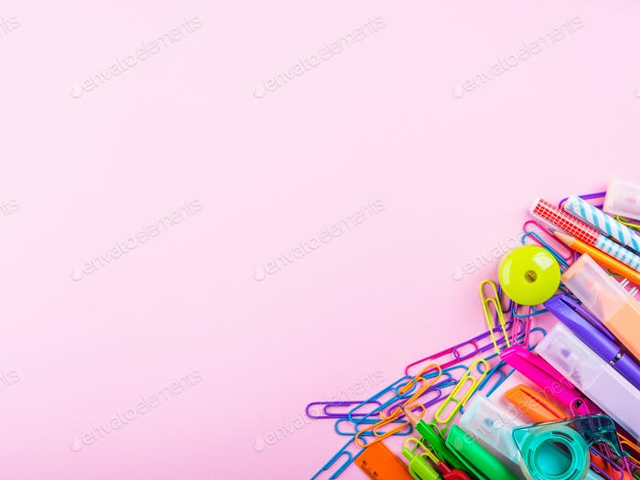 Colorful stationery office supply frame on pink