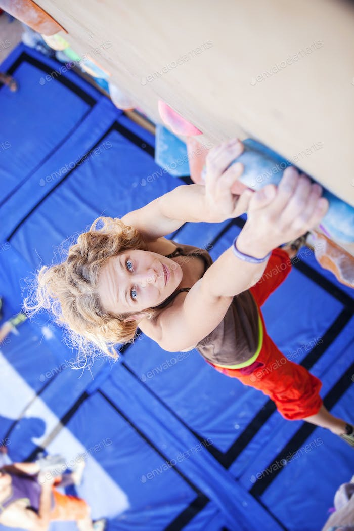 Female climber holding gripping top handhold on artificial climbing wall