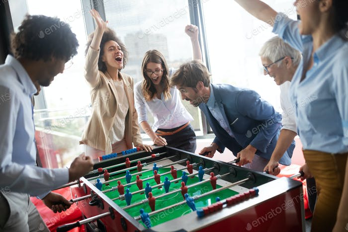 Multicultural business people celebrating win while playing table football