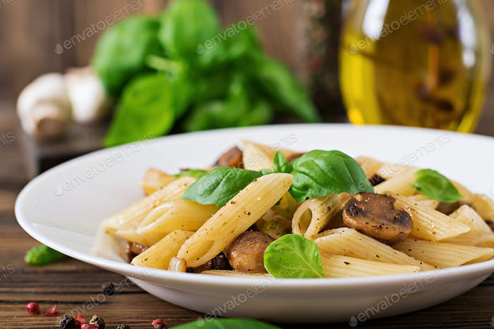 Vegetarian Vegetable pasta penne  with mushrooms  in white bowl on wooden table. Vegan food.