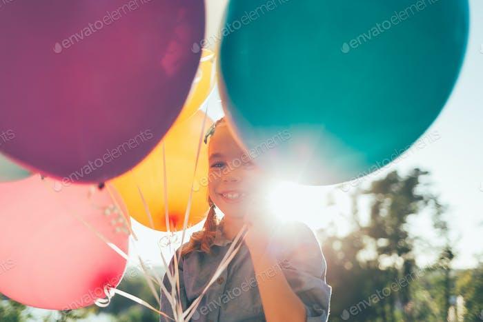 Porträt von niedlichen Mädchen lächelnd zeigt Zähne umgeben von farb