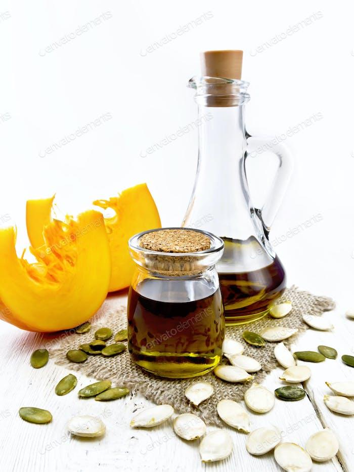 Oil pumpkin in jar and carafe on board