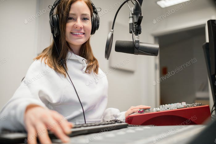 Radio Jockey lächelnd beim Tragen von Kopfhörern im Studio