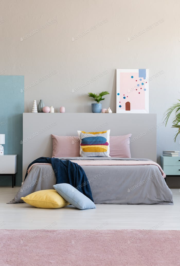 Blanket on bed in colorful bedroom interior with poster and plan