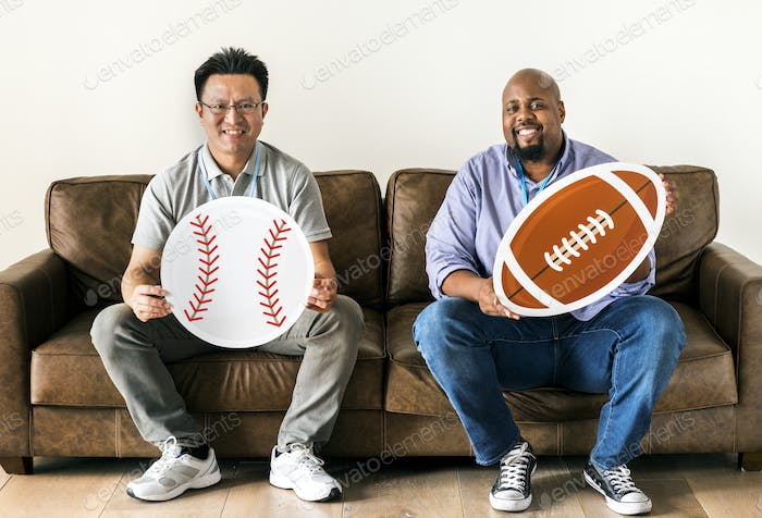 Men holding baseball and rugby icons sitting on couch