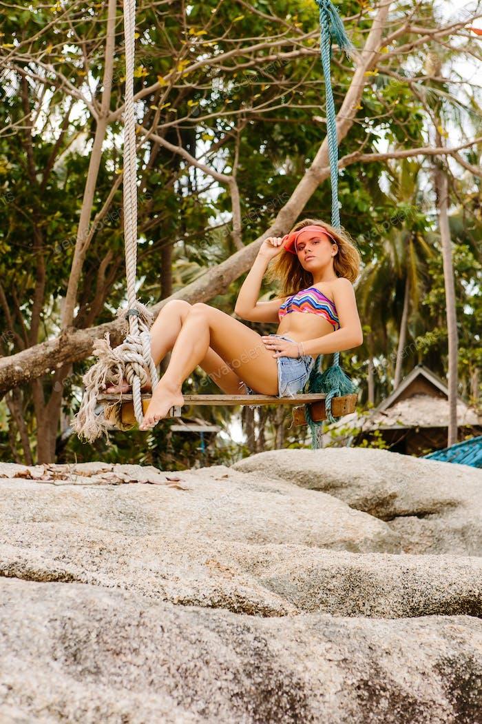 Beautiful woman on swing in tropics.