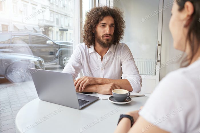 Indoor shot of handsome curly guy with beard having important conversation with business partner
