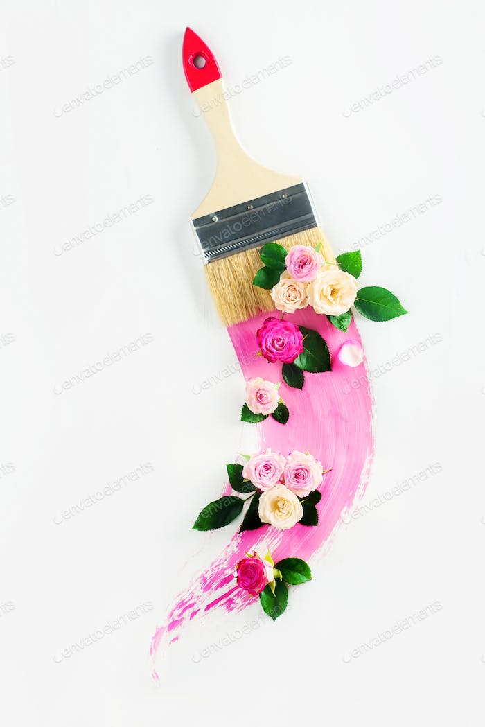 Creative spring transfiguration concept with flowers, paint brush and a swoosh of pink color. High
