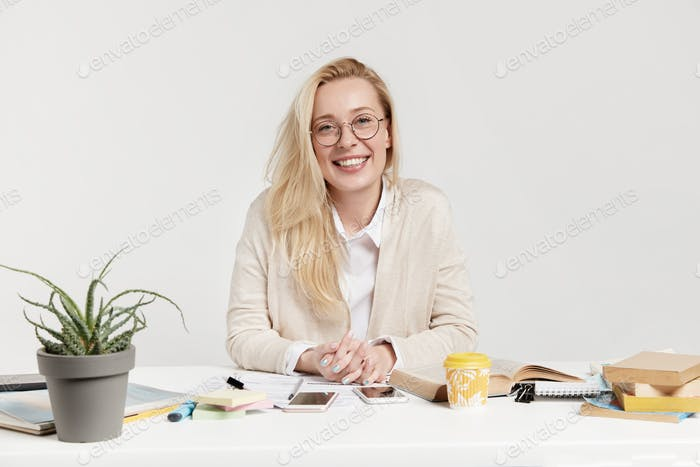 Confident happy pleasant looking woman sits at workplace with books and papers, works at home, prepa