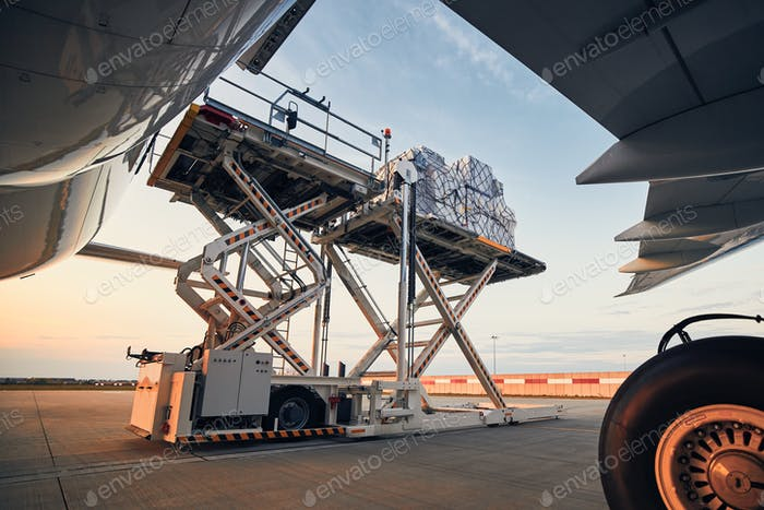 Loading of cargo containers to airplane at sunset