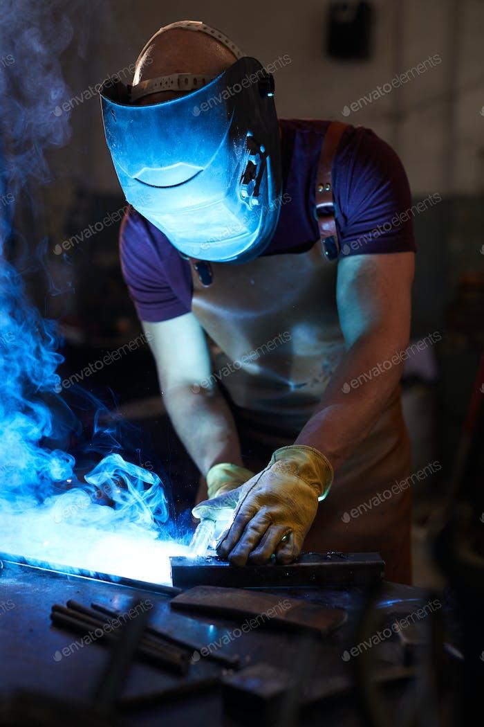 Workman welding metal