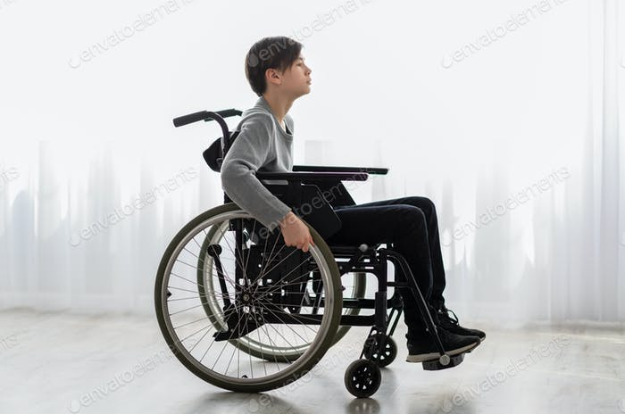 Full length portrait of impaired teenage boy sitting in wheelchair at home, side view
