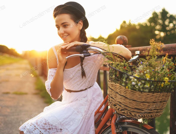 Young beautiful woman sitting on her bicycle with flowers at sun