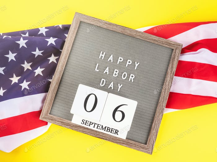 Happy Labor Day greetings on letter board with american flag