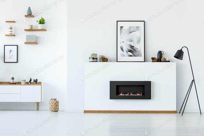Black lamp next to fireplace under posters in minimal white livi