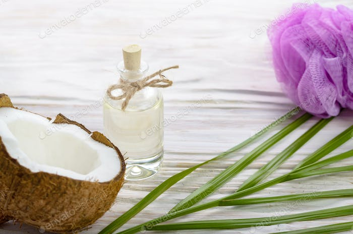 Coconut oil in glass bottle bath sponge and shell pieces on whit