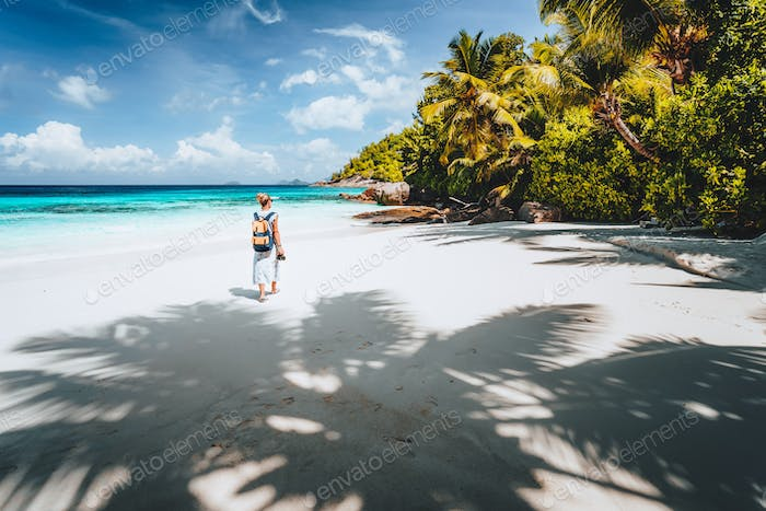 Female tourist enjoy empty tropical beach on vacation. White sand beach, palm trees and blue ocean