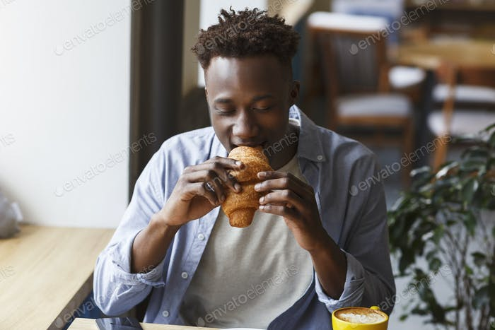 Modern lifestyle. African American man eating croissant for lunch in coffee shop