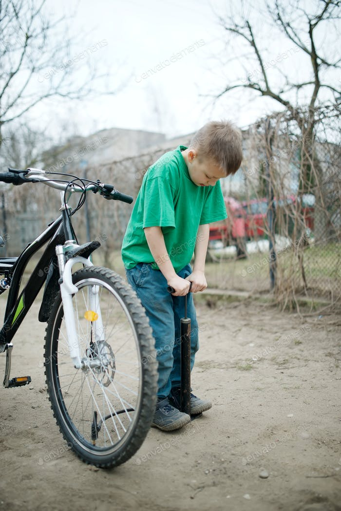 boy pumps up his bicycle wheel