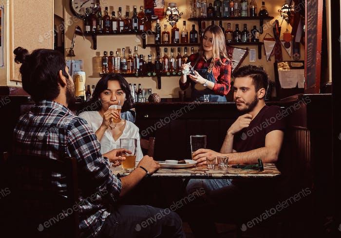 Молодые мультирасовые друзья отдыхают в пабе.