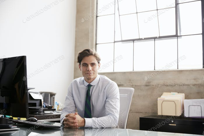Young businessman sitting at office desk smiling to camera