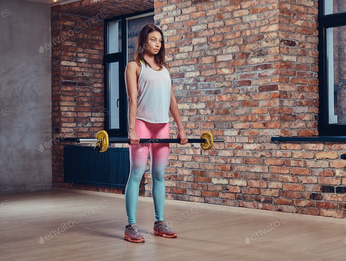 A woman holds barbell.