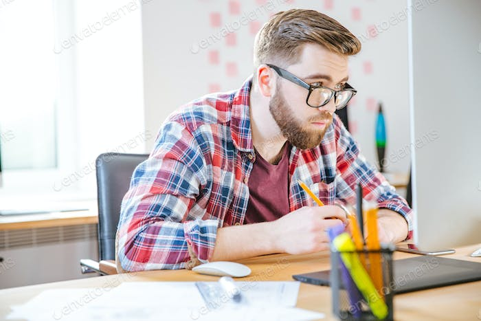 Serious man sitting on workplace and looking over glasses