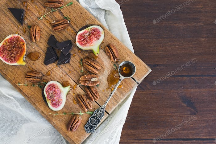 Fresh figs and pekan nuts with honey on a wooden board