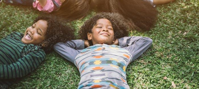 Happy children kids laying on grass in park