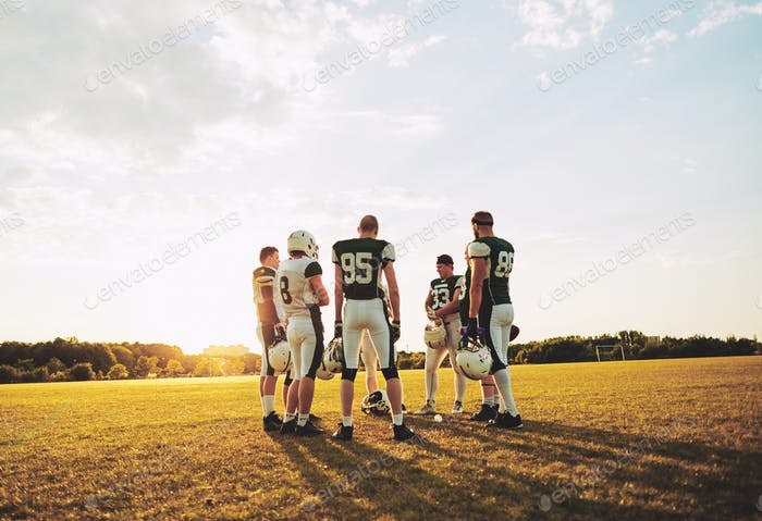American football standing together on a field during practice