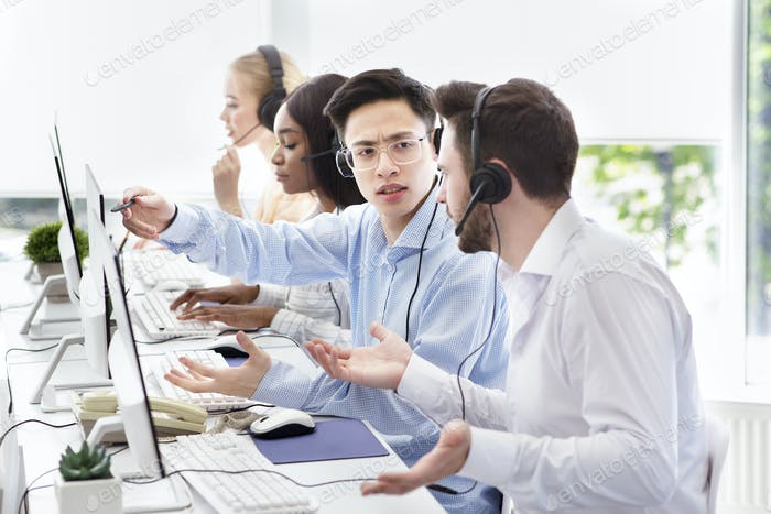 User support service concept. Hotline operator helping his coworker at call centre