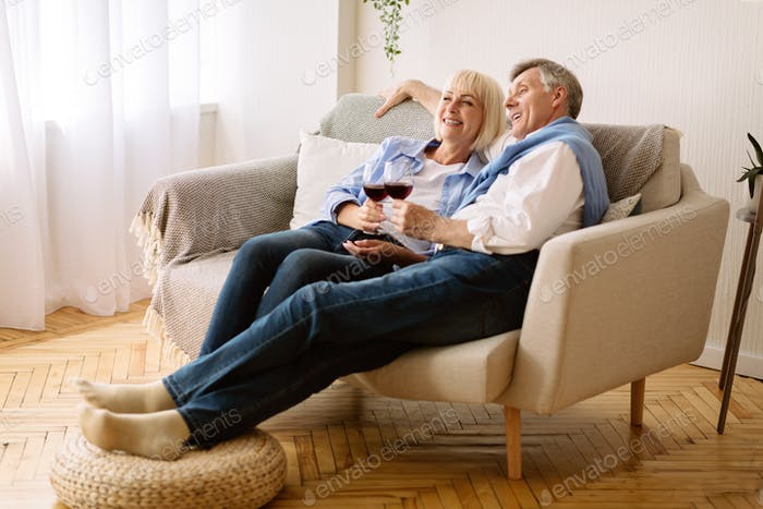 Happy retirement. Senior couple drinking wine and watching tv