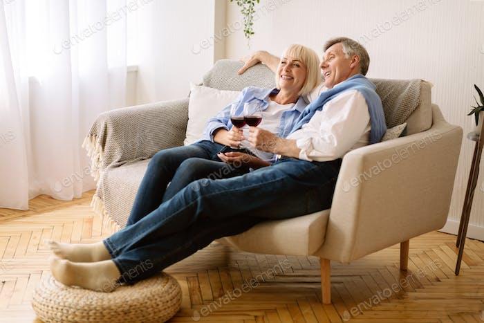 Feliz retiro. Senior pareja bebiendo vino y viendo tv
