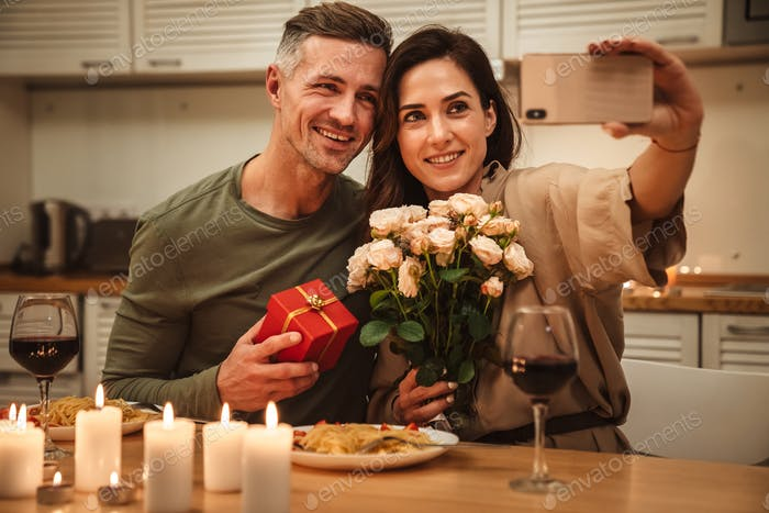 Image of couple taking selfie while having candlelight dinner at home
