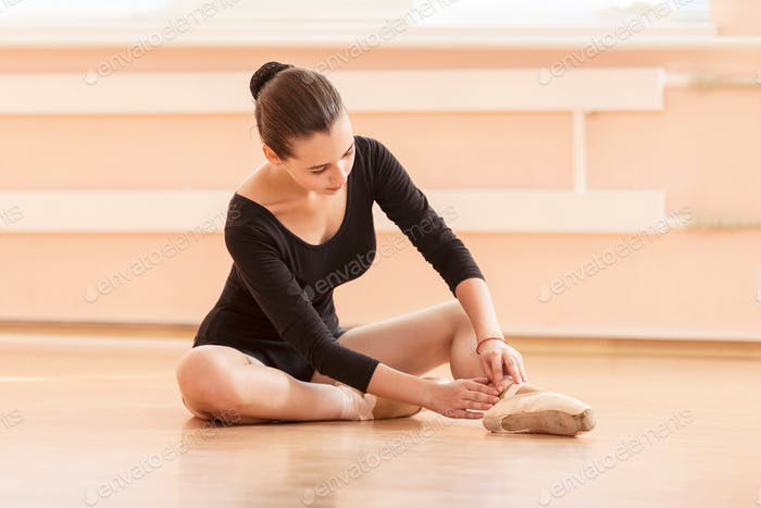 Young ballet dancer putting on pointe shoes while sitting on floor