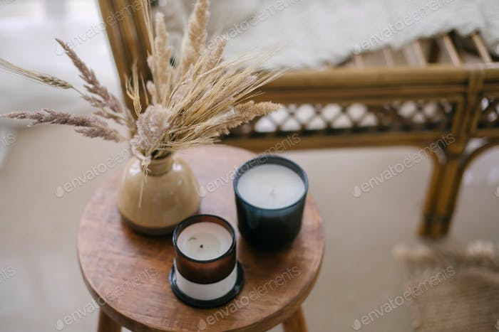 Home interior decor in beige neutral colors. Wooden table with dried flowers in vase and candle