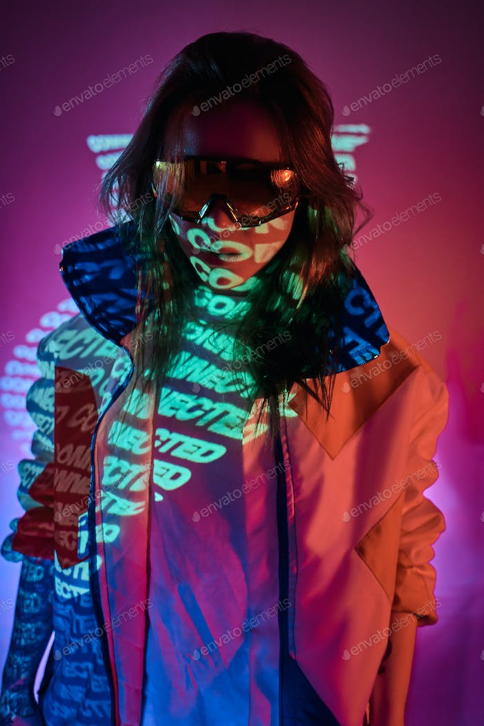 Portrait of a tattooed racer woman hiding her face in the collar of a coat in a vivid neon studio