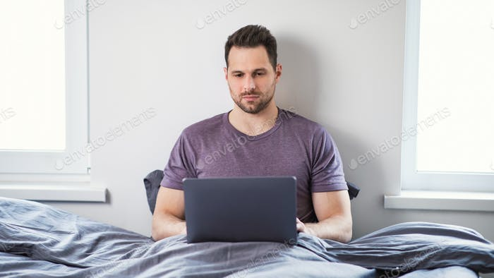 Freelancer Man Working On Laptop Online Sitting In Bed Indoor