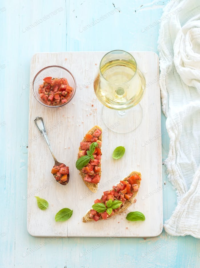 Tomato and basil bruschetta sandwich on white wooden serving board