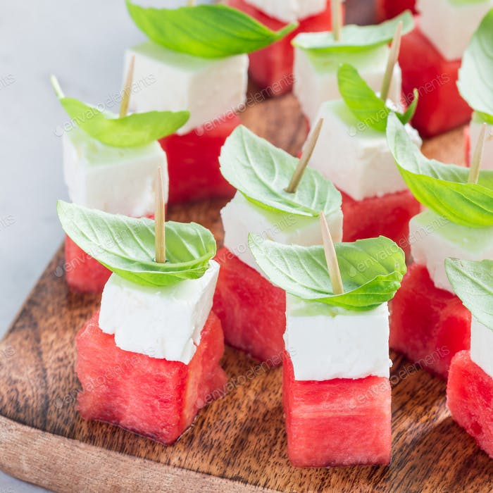 Watermelon salad or caprese with watermelon, feta and basil on a wooden board, square