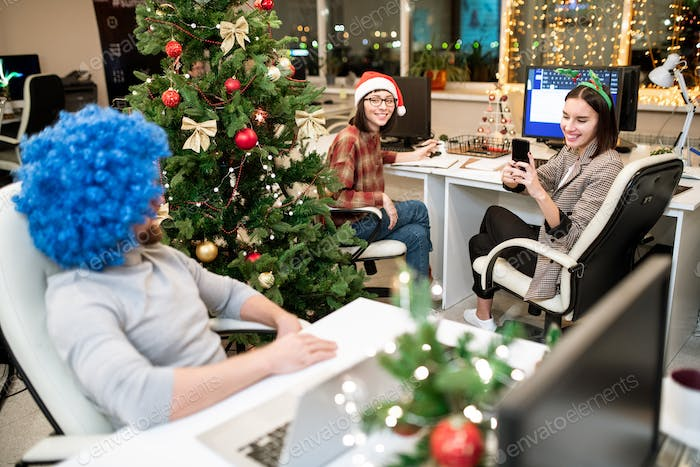 One of young happy businesswomen taking photo of colleague in blue wig