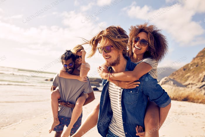 Young couple playing piggyback on beach