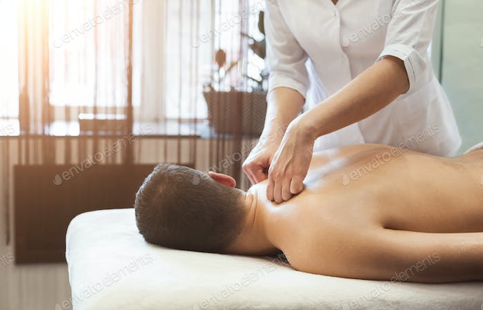 Woman massaging male shoulders and back