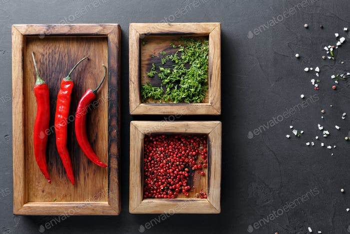 Diverse spices and chilli in wooden boxes on dark background, top view, copy space