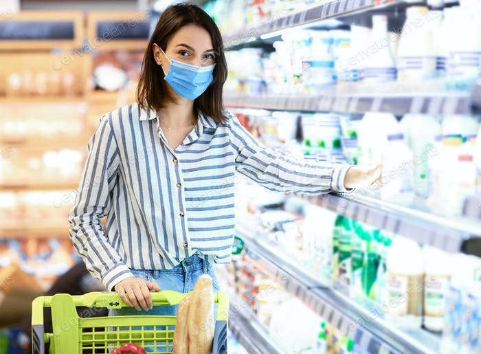 Woman in medical mask shopping groceries, buying milk