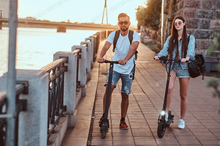 Two friends are enjoying summer day with their electro scooters