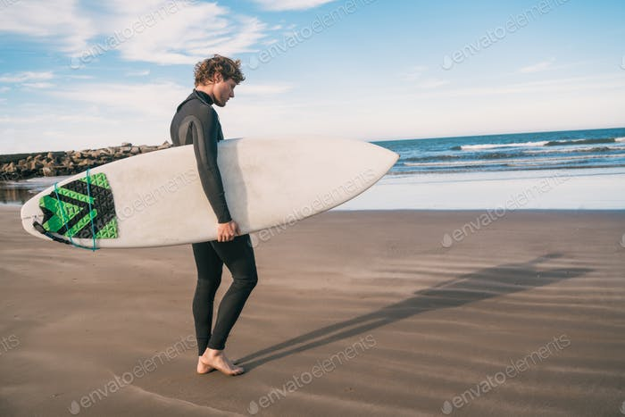 Surfer standing in the ocean with his surfboard.